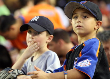 NEW YORK - JUNE 27: Young fans of the New York Yankees and the New York Mets watch at Shea Stadium on June 27, 2008 in the Flushing neighborhood of the Queens borough of New York City.  (Photo by Michael Heiman/Getty Images)