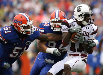 GAINESVILLE, FL - NOVEMBER 15:  Linebacker Brandon Spikes #51 and defensive end Justin Trattou #94 of the Florida Gators bring down wide receiver Kenny McKinley #11 of the South Carolina Gamecocks at Ben Hill Griffin Stadium on November 15, 2008 in Gaines