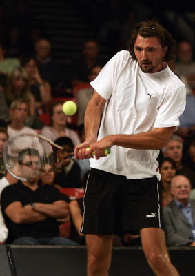 LONDON - OCTOBER 3:  Goran Ivanisevic of Croatia in action against Tommy Robredo of Spain during the first round of the Superset Tennis tournament at Wembley Arena on October 3, 2004 in London.  (Photo by Paul Gilham/Getty Images)