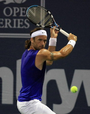 LOS ANGELES, CA - AUGUST 5:  Carlos Moya of Spain returns to Xavier Malisse of Belgium during the Countrywide Classic Day 2 at Los Angeles Tennis Center - UCLA August 5, 2008 in Los Angeles, California.  (Photo by Jonathan Moore/Getty Images)