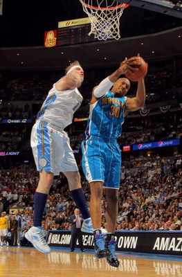 DENVER - APRIL 29:  David West #30 of the New Orleans Hornets grabs a rebound away from Chris Andersen #11 of the Denver Nuggets in Game Five of the Western Conference Quarterfinals during the 2009 NBA Playoffs at Pepsi Center on April 29, 2009 in Denver,