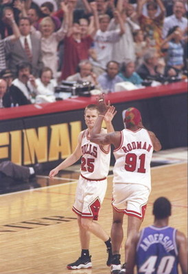 13 Jun 1997: Guard Shandon Anderson of the Utah Jazz watches as guard Steve Kerr #25 and forward Dennis Rodman #91 of the Chicago Bulls high five each other during game 6 of the 1997 NBA Finals at the United Center in Chicago, Illinois. The Bulls defeated