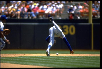 TONY FERNANDEZ, SHORTSTOP FOR THE TORONTO BLUE JAYS, STUMBLES WHILE ATTEMPTING TO PICK UP A GROUND BALL DURING THEIR GAME AGAINST THE OAKLAND A''S AT THE OAKLAND COLISEUM IN OAKLAND, CALIFORNIA. MANDATORY CREDIT: OTTO GREULE/ALLSPORT