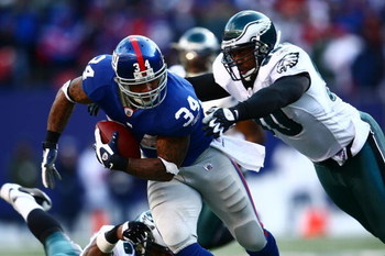 EAST RUTHERFORD, NJ - JANUARY 11: Derrick Ward #34 of the New York Giants runs against Darren Howard #90 of the Philadelphia Eagles during the NFC Divisional Playoff Game on January 11, 2009 at Giants Stadium in East Rutherford, New Jersey.  (Photo by Chr