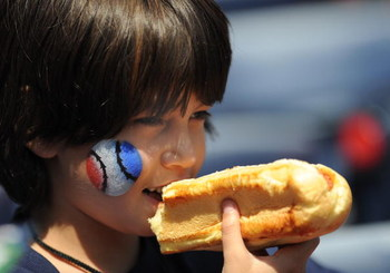 ATLANTA - APRIL 12: A young baseball fan enjoys a hot dog as the Atlanta Braves host the Washington Nationals April 12, 2009 at Turner Field in Atlanta, Georgia.  (Photo by Al Messerschmidt/Getty Images)
