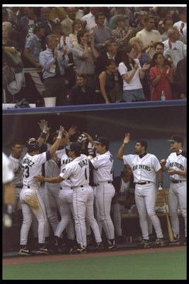 6 Oct 1995: Tino Martinez of the Seattle Mariners is congratulated by his team in the dug out after hitting a home run against the New York Yankees in the Divisional Playoffs of the American League at the King Dome in Seattle, Washington. The Mariners d