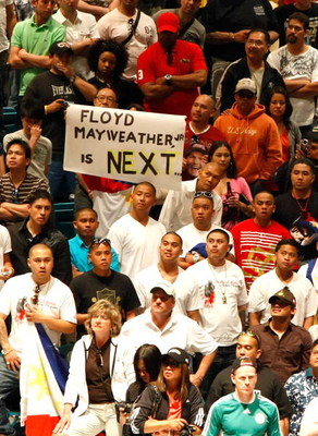 LAS VEGAS - MAY 01:  A sign for Floyd Mayweather Jr. is held as boxing fans wait for the official weigh-in for the junior welterweight title fight between Ricky Hatton of England and Manny Pacquiao of the Philippines at the MGM Grand Garden Arena May 1, 2