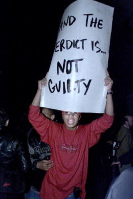 386798 06: A supporter shouts while holding a sign announcing the not guilty verdict against rap music mogul Sean 'Puffy' Combs outside Manhattan State Supreme Court March 16, 2001 in New York, Friday. (Photo by Robert Mecea/Newsmakers)