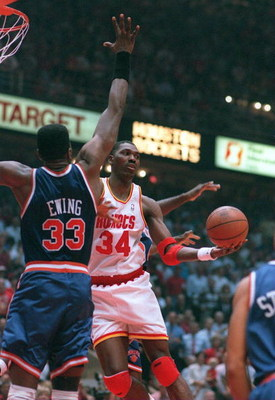 22 JUN 1994:  HOUSTON ROCKET HAKEEM OLAJUWON DISHES A PASS AROUND NEW YORK KNICK PATRICK EWING DURING THE FIRST QUARTER OF GAME SEVEN IN THE NBA CHAMPIONSHIPS AT THE SUMMIT IN HOUSTON. Mandatory Credit: Allsport/ALLSPORT