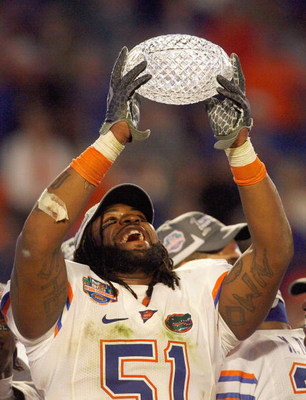 MIAMI - JANUARY 08:  Brandon Spikes #51 of the Florida Gators holds up the winning trophy after the FedEx BCS National Championship Game against the Oklahoma Sooners at Dolphin Stadium on January 8, 2009 in Miami, Florida.  (Photo by Eliot J. Schechter/Ge