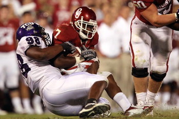 NORMAN, OK - SEPTEMBER 27:  Running back DeMarco Murray #7 of the Oklahoma Sooners is tackled by Jerry Hughes #98 of the TCU Horned Frogs at Memorial Stadium on September 27, 2008 in Norman, Oklahoma.  (Photo by Ronald Martinez/Getty Images)