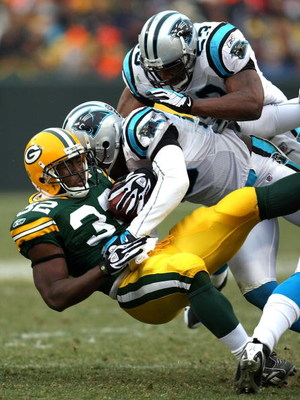 GREEN BAY, WI - NOVEMBER 30:  Brandon Jackson #32 of the Green Bay Packers is tackled by Thomas Davis #58 and Na'il Diggs #53 of the Carolina Panthers at Lambeau Field on November 30, 2008 in Green Bay, Wisconsin.  (Photo by Jonathan Daniel/Getty Images)