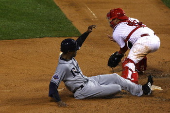 PHILADELPHIA - OCTOBER 27:  B.J. Upton #2 of the Tampa Bay Rays scores on a RBI single by Carlos Pena  in the top of the sixth inning against Carlos Ruiz #51 of the Philadelphia Phillies during game five of the 2008 MLB World Series on October 27, 2008 at