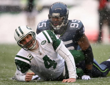 SEATTLE - DECEMBER 21:  Quarterback Brett Favre #4 of the New York Jets looks up after being tackled by Lawrence Jackson #95 of the Seattle Seahawks on December 21, 2008 at Qwest Field in Seattle, Washington. The Seahawks defeated the Jets 13-3. (Photo by