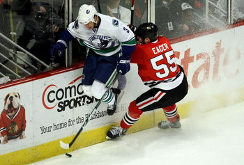 CHICAGO - MAY 05:  Kevin Bieksa #3 of the Vancouver Canucks avoids an attempted check by Ben Eager #55 of the Chicago Blackhawks during the first period of Game Three of the Western Conference Semifinal Round of the 2009 Stanley Cup Playoffs on May 5, 200