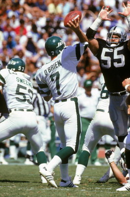 LOS ANGELES, CA - SEPTEMBER 8:  Quarterback Ken O'Brien #7 of the New York Jets sets to throw a pass over the arms of Matt Millen #55 of the Los Angeles Raiders during a game at the Los Angeles Memorial Coliseum on September 8, 1985 in Los Angeles, Califo