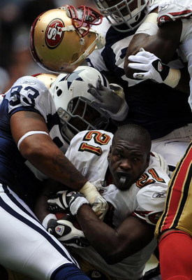IRVING, TX - NOVEMBER 23:  Running back Frank Gore #21 of the San Francisco 49ers loses his helmet while tackled by Anthony Spencer #93 of the Dallas Cowboys at Texas Stadium on November 23, 2008 in Irving, Texas.  (Photo by Ronald Martinez/Getty Images)