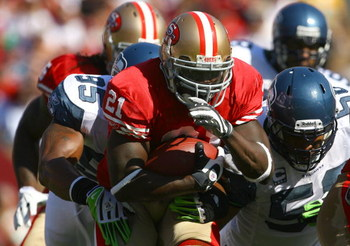 SAN FRANCISCO - OCTOBER 26:  Runningback Frank Gore #21 of the San Francisco 49ers carries the ball while being pursued by Lawrence Jackson #95 of the Seattle Seahawks in the first quarter at Candlestick Park on October 26, 2008 in San Francisco, Californ