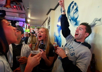 NEW YORK - APRIL 16:  Yankees fans celebrate in the famous Stan's bar near the new Yankee Stadium before the first pitch on opening day April 16, 2009 in the Bronx borough of New York City. The New York Yankees are playing against the Cleveland Indians in