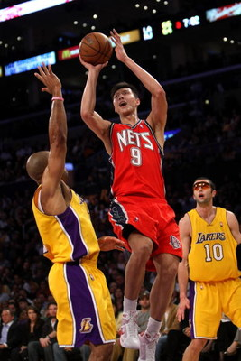LOS ANGELES, CA - NOVEMBER 25:  Yi Jianlian #9 of the New Jersey Nets shoots over Derek Fisher #2 of the Los Angeles Lakers on November 25, 2008 at Staples Center in Los Angeles, California. The Lakers won 120-93.   NOTE TO USER: User expressly acknowledg