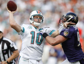 MIAMI - JANUARY 04:  Chad Pennington #10 of the Miami Dolphins tries to get a first quarter pass off around Jarret Johnson #95 of the Baltimore Ravens during the AFC Wild Card playoff game on January 4, 2009 at Dolphin Stadium in Miami, Florida.  (Photo b