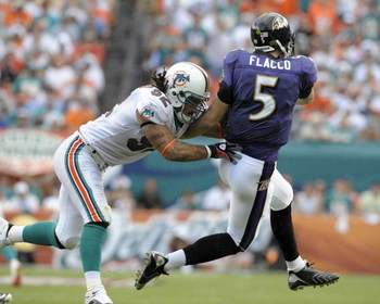 MIAMI, FL - JANUARY 4:  Linebacker Channing Crowder #52 of the Miami Dolphins hits quarterback Joe Flacco #5 of the Baltimore Ravens in an AFC wild card game at Dolphins Stadium January 4, 2009 in Miami, Floirda.  (Photo by Al Messerschmidt/Getty Images)