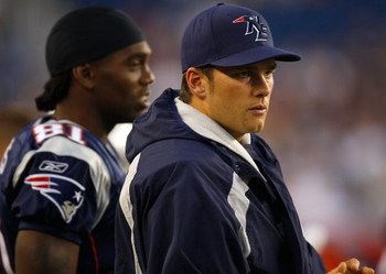 FOXBORO, MA - AUGUST 7:  Randy Moss #81 and Tom Brady #12 of the New England Patriots watch the game on the sidelines against the Baltimore Ravens during a preseason game at Gillette Stadium on August 7, 2008 in Foxboro, Massachusetts. (Photo by Jim Rogas