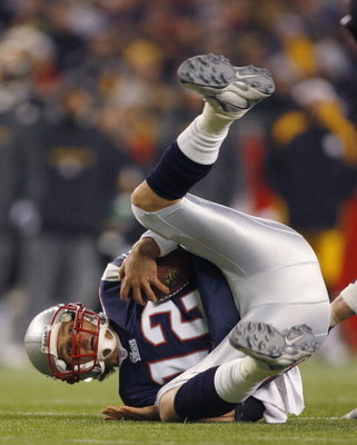 FOXBORO, MA - DECEMBER 9:   Tom Brady #12 of the New England Patriots tumbles after being pressed by the defense of the Pittsburgh Steelers at Gillette Stadium December 9, 2007 in Foxboro, Massachusetts. The Patriots won 34-13.  (Photo by Jim Rogash/Getty