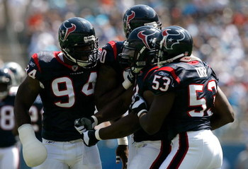 CHARLOTTE, NC - SEPTEMBER 16:  Defenders N. D. Kalu #94, Mario Williams #90 and Shantee Orr #53 of the Houston Texans celebrate with Amobi Okoye #91 after Okoye recorded a sack against the Carolina Panthers during the first half at Bank of America Stadium