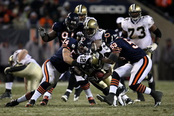 CHICAGO - DECEMBER 11:  Marques Colston #12 of the New Orleans Saints is tackled by Brian Urlacher #54, Tommie Harris #91 and Nick Roach #53 of the Chicago Bears at Soldier Field on December 11, 2008 in Chicago, Illinois. The Bears won 27-24. (Photo by Jo