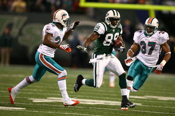 EAST RUTHERFORD, NJ - DECEMBER 28: Jerricho Cotchery #89 of The New York Jets runs after a catch as Renaldo Hill #24 and Yeremiah Bell #37 of The Miami Dolphins chase during their game on December 28, 2008 at Giants Stadium in East Rutherford, New Jersey.