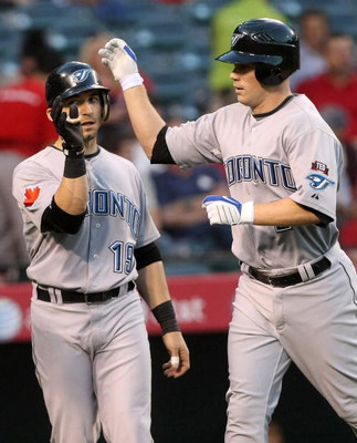 ANAHEIM, CA - MAY 6:  Aaron Hill #2 of the Toronto Blue Jays is greeted at home plate by Marco Scutaro #19 after both scored on Hill's first inning home run against the Los Angeles Angels of Anaheim at Angel Stadium May 6, 2009 in Anaheim, California.  (P