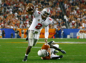 GLENDALE, AZ - JANUARY 05:  Quarterback Terrelle Pryor #2 of the Ohio State Buckeyes scrambles with the ball under pressure from Ryan Palmer #13 of the Texas Longhorns during the Tostitos Fiesta Bowl Game on January 5, 2009 at University of Phoenix Stadiu