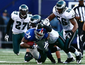 EAST RUTHERFORD, NJ - JANUARY 11: Derrick Ward #34 of the New York Giants runs against Trent Cole #58, Akeem Jordan #56 and Quintin Mikell #27 of the Philadelphia Eagles during the NFC Divisional Playoff Game on January 11, 2009 at Giants Stadium in East