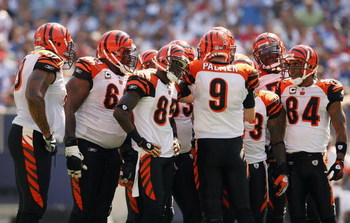 EAST RUTHERFORD, NJ - SEPTEMBER 21:  Carson Palmer #9  of the Cincinnati Bengals talks in the huddle as teammates Chad 'Ocho Cinco' Johnson #85 and T.J. Houshmandzadeh #84 listen during the first half of the game against the New York Giants on September 2