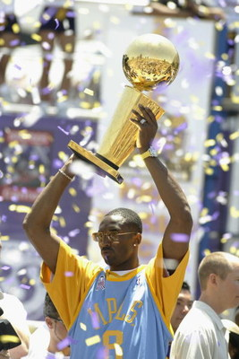 LOS ANGELES - JUNE 14: Kobe Bryant #8 of the Los Angeles Lakers holds up the Larry O'Brien trophy on stage in downtown Los Angeles following the victory parade on June 14, 2002 at Staples Center in Los Angeles, California.  The Lakers won their third cons