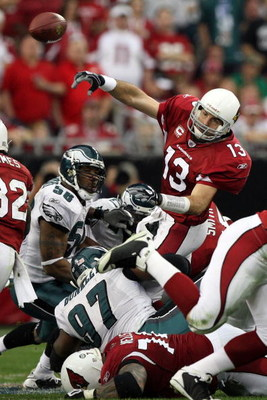 GLENDALE, AZ - JANUARY 18:  Quarterback Kurt Warner #13 of the Arizona Cardinals throws the ball as he is hit by Philadelphia Eagles defenders during the NFC championship game on January 18, 2009 at University of Phoenix Stadium in Glendale, Arizona.  (Ph