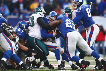 EAST RUTHERFORD, NJ -  JANUARY 11:  Eli Manning #10 of the New York Giants is tackled by Mike Patterson #98 of the Philadelphia Eagles during the NFC Divisional Playoff Game on January 11, 2009 at Giants Stadium in East Rutherford, New Jersey.  The Eagles