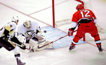 RALEIGH, NC - MAY 23:  Rob Scuderi #4 defends as goaltender Marc-Andre Fleury #29 of the Pittsburgh Penguins saves a shot on goal by Eric Staal #12 of the Carolina Hurricanes during Game Three of the Eastern Conference Championship Round of the 2009 Stanl