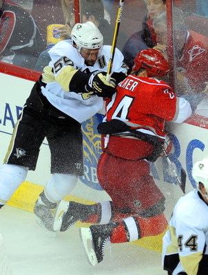 RALEIGH, NC - MAY 23:  Sergei Gonchar #55 of the Pittsburgh Penguins checks Scott Walker #24 of the Carolina Hurricanes into the boards during Game Three of the Eastern Conference Championship Round of the 2009 Stanley Cup Playoffs at RBC Center on May 23