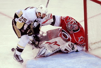 RALEIGH, NC - MAY 23:  Maxime Talbot #25 of the Pittsburgh Penguins attacks as goaltender Cam Ward #30 of the Carolina Hurricanes saves a shot on goal during Game Three of the Eastern Conference Championship Round of the 2009 Stanley Cup Playoffs at RBC C