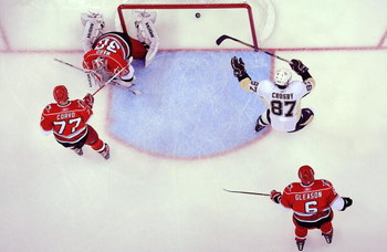 RALEIGH, NC - MAY 23:  Sidney Crosby #87 of the Pittsburgh Penguins scores a goal past goaltender Cam Ward #30, Joe Corvo #77 and Tim Gleason #6 of the Carolina Hurricanes during Game Three of the Eastern Conference Championship Round of the 2009 Stanley 