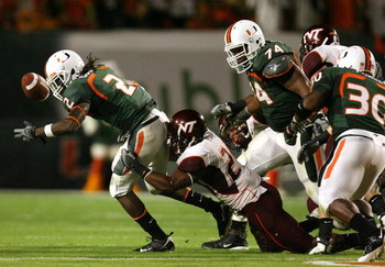 MIAMI - NOVEMBER 13:  Dorian Porch #24 of the Virginia Tech Hokies causes a fumble by running back Craig Cooper #2 of the Miami Hurricanes at Dolphin Stadium on November 13, 2008 in Miami, Florida. Miami defeated Virginia Tech 16-14.  (Photo by Doug Benc/