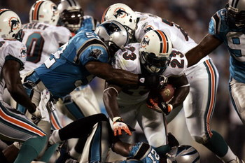 CHARLOTTE, NC - AUGUST 24:  Running back Ronnie Brown #23 of the Miami Dolphins is tackled by the Carolina Panthers during the preseason game at Bank of America Stadium in Charlotte, North Carolina, on August 24, 2006. The Panthers won 19-10.  (Photo by D