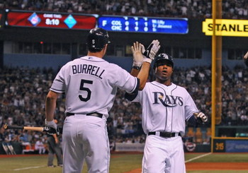 ST. PETERSBURG, FL - APRIL 13: Designated hitter Pat Burrell #5 of the Tampa Bay Rays high fives outfielder Carl Crawford #13 against the New York Yankees on April 13, 2009 at Tropicana Field in St. Petersburg, Florida.  (Photo by Al Messerschmidt/Getty I