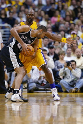 LOS ANGELES - MAY 11:  Tim Duncan #21 of the San Antonio Spurs is covered by Karl Malone #11 of the Los Angeles Lakers in Game four of the Western Conference Semifinals during the 2004 NBA Playoffs at Staples Center on May 11, 2004 in Los Angeles, Califor