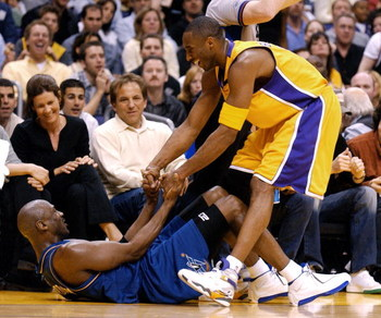 LOS ANGELES - MARCH 28:  Kobe Bryant #8 of the Los Angeles Lakers helps up Michael Jordan#23 of the Washington Wizards during the game between the Washington Wizards and the Los Angeles Lakers on March 28, 2003 at the Staples Center in Los Angeles, Califo