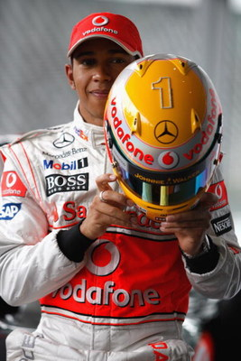 WOKING, ENGLAND - MAY 14:  Lewis Hamilton of Great Britain and team McLaren Mercedes shows of the Steinmetz diamonds that are embedded in his racing helmet at a photo call at Paragon, headquarters of the McLaren Group, on May 14, 2009, in Woking, England