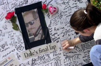 385860 08: A woman signs a condolence card at a makeshift memorial for NASCAR driver Dale Earnhardt, February 21, 2001 at Atlanta Motor Speedway in Hampton, Georgia. Earnhardt was killed February 18, 2001 in a crash on the final lap of the Daytona 500. (P