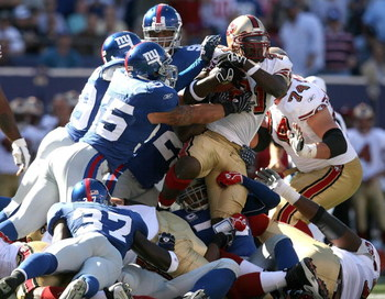 EAST RUTHERFORD, NJ - OCTOBER 21:  Frank Gore #21 of the San Francisco 49ers is tackled by the New York Giants on October 21, 2007 at Giants Stadium in East Rutherford, New Jersey.  (Photo by Nick Laham/Getty Images)